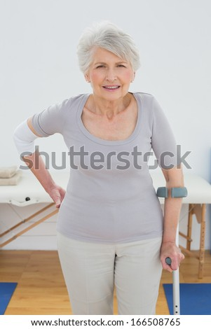 Portrait of a senior woman with crutch standing in the hospital gym - stock photo