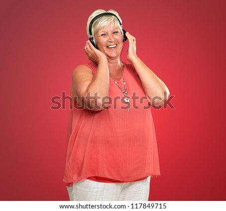 Portrait Of A Senior Woman With Headphone On Red Background - stock photo