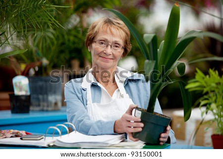 Portrait of a senior woman working in a garden center - stock photo