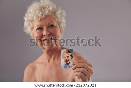 Portrait of a senior women holding her old photo. Beautiful woman shirtless showing a vintage photograph of her young age. Memory of her young days. - stock photo