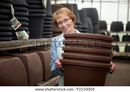 Portrait of a senior worker in garden center with large plant pots - stock photo