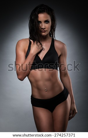 Portrait of a Sensual Athletic Woman in Black Underwear, Touching her Face While Looking at the Camera. Captured in Studio with Fuzzy Brick Wall Background. - stock photo