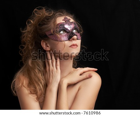 portrait of a sensual beautiful blond young woman with purple carnival mask, role play - stock photo
