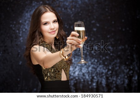 Portrait of a sensual beautiful young brunette woman holding a glass of champagne. - stock photo