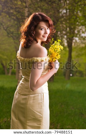 portrait of a sensual  brunette caucasian girl in wedding dress standing with flowers in spring forest-outside