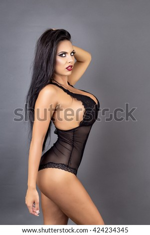 Portrait of a sensual brunette woman posing in sexy black lingerie over gray background