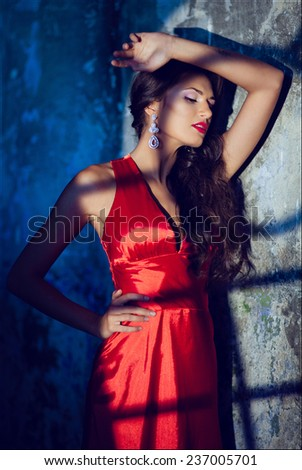 Portrait of a sensual sexy beautiful curly girl in a red dress with a shadow from the window