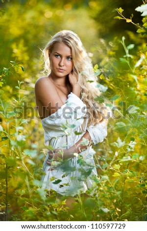 Portrait of a sensual young blonde female on field in sexy white short dress - stock photo