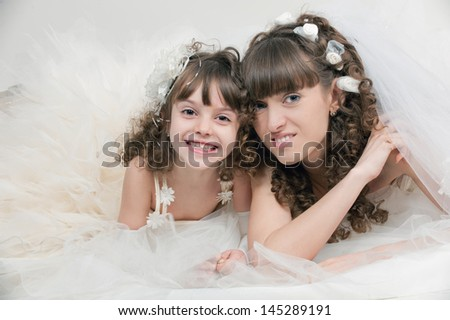 Portrait of a sensual young mother and daughter in a beautiful wedding dress posing in studio on white