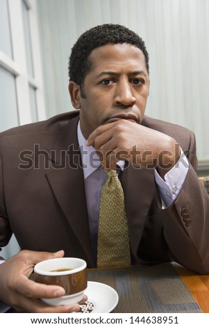 Portrait of a serious African American businessman with coffee cup at office table - stock photo