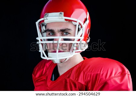 Portrait of a serious american football player taking his helmet looking at camera with black background - stock photo