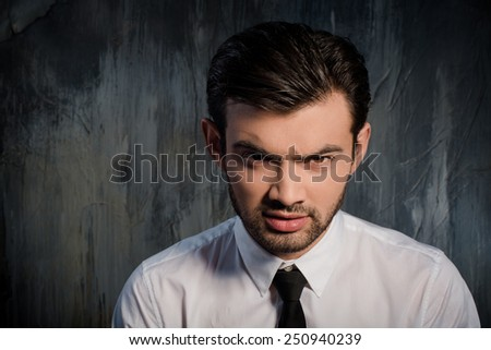 Portrait of a serious and gloomy man on gray background