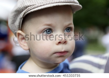 Portrait of a serious boy in cap in summer park - stock photo