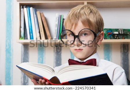 Portrait of a serious boy in the bow tie with the book at home - stock photo