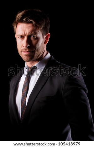 portrait of a serious business man looking straight to the camera - stock photo