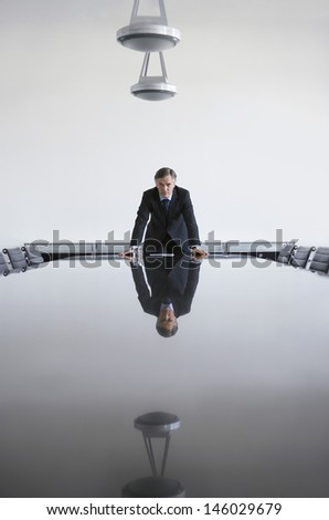 Portrait of a serious businessman standing at conference table - stock photo