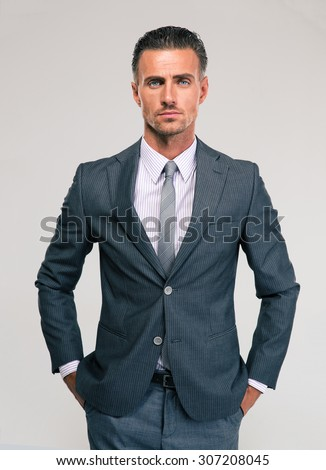 Portrait of a serious businessman standing isolated on a white background. Looking at camera - stock photo