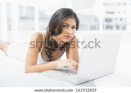 Portrait of a serious casual young woman using laptop in bed at home