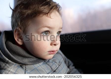 Portrait of a serious child in the car - stock photo