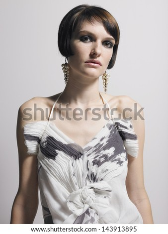 Portrait of a serious elegant woman in dress against gray background - stock photo