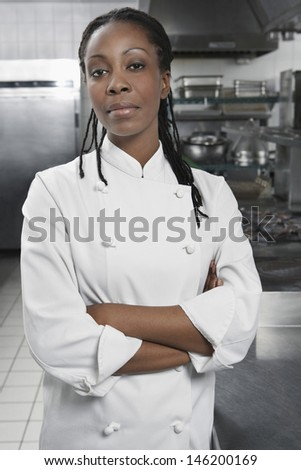 Portrait of a serious female chef with hands crossed in the kitchen - stock photo