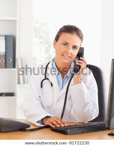 Portrait of a serious female doctor on the phone in her office - stock photo