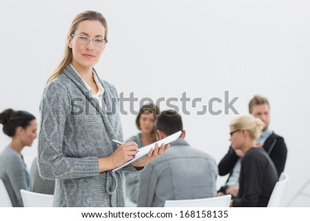 Portrait of a serious female therapist with group therapy in session in background - stock photo