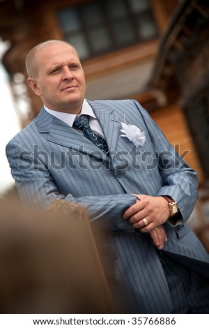 Portrait of a serious groom on the blurred background. Focus point on the groom's face. - stock photo