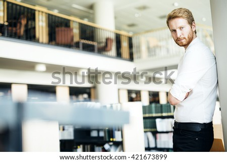 Portrait of a serious handsome student in library - stock photo