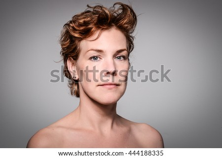 Portrait of a serious, independent, mature and thoughtful red haired woman. Female model looking sad or depressed. - stock photo
