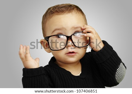 portrait of a serious kid wearing glasses and doing a gesture over a grey background - stock photo