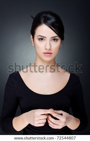 portrait of a serious lady with beautiful makeup over dark background - stock photo