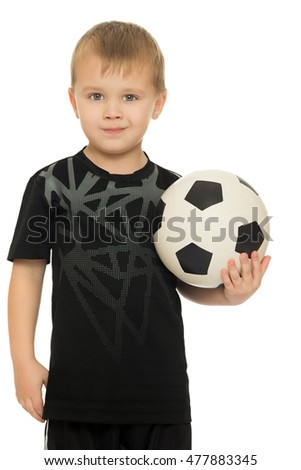 Portrait of a serious little boy football player in black uniform. The boy holds a hand soccer ball. Close-up - Isolated on white background
