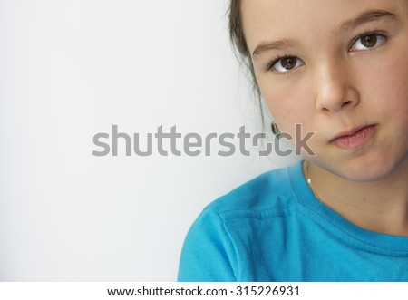 Portrait of a serious little girl on a gray background - stock photo