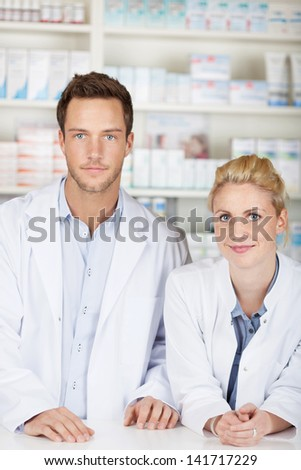 Portrait of a serious male and female pharmacists in front of medicines at drugstore