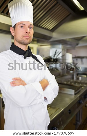 Portrait of a serious male cook with arms crossed standing in the kitchen
