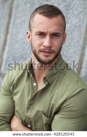Portrait of a serious man in a green shirt posing on a stone wall background - stock photo