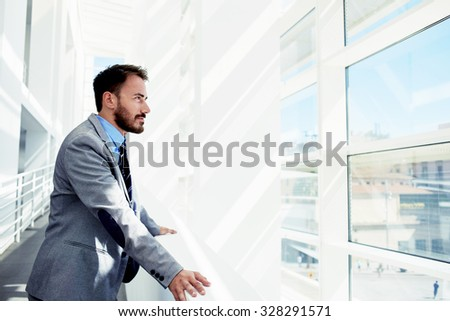 Portrait of a serious man office worker dressed in elegant clothes watching in window while standing in modern office space, thoughtful young male entrepreneur in suit resting after business meeting - stock photo