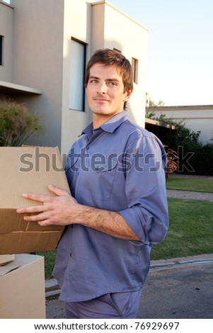 Portrait of a serious man outdoors with cardboard moving boxes - stock photo