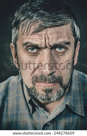 Portrait of a serious man with a beard - stock photo
