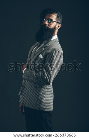 Portrait of a Serious Man with Long Goatee Beard Posing in Formal Suit with Eyeglasses and Looking at the Camera on Black background. - stock photo