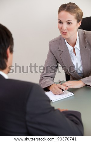 Portrait of a serious manager interviewing a male applicant in her office - stock photo