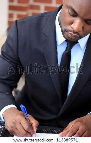 Portrait of a Serious, Mature, and Attractive, Young Professional African American Businessman Working On Paperwork - stock photo