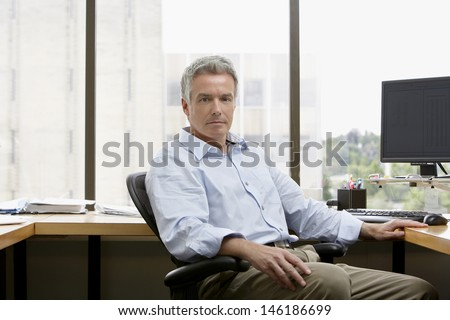 Portrait of a serious mature businessman sitting at office desk - stock photo