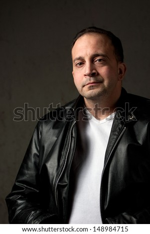 Portrait of a serious middle aged man in his upper 30s wearing a leather jacket in front of a grungy background. - stock photo