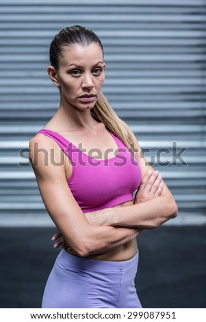 Portrait of a serious muscular woman with hands on hips - stock photo