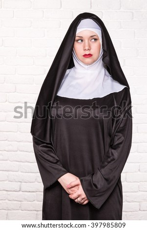 Portrait of a serious nuns standing near a white brick wall - stock photo