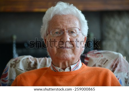 Portrait of a serious old man in his house - stock photo