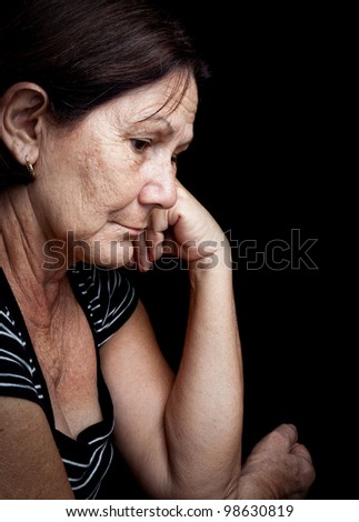 Portrait of a serious old woman with a worried expression isolated on black - stock photo