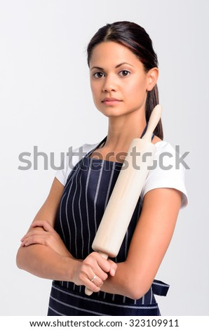 Portrait of a serious professional baker holding a rolling pin, isolated on grey background